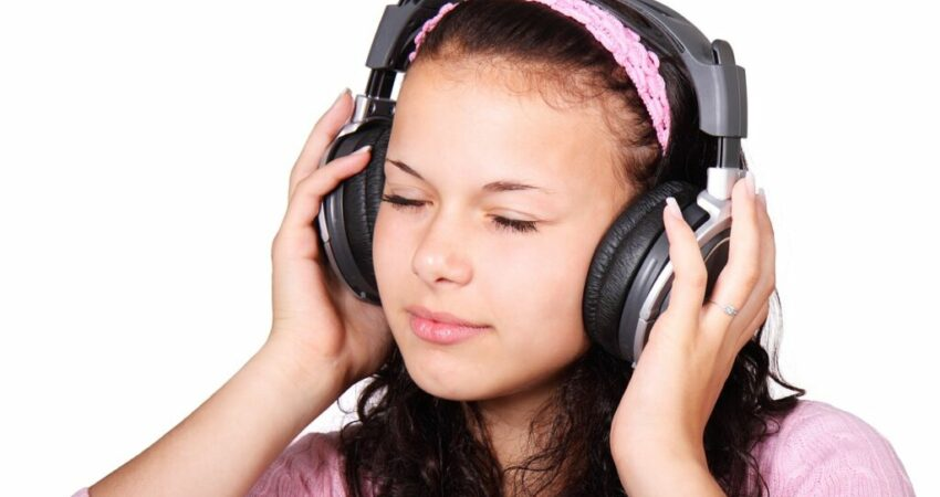 Woman relaxing while listening to a podcast on her headphone