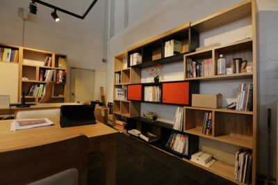 A small office with built-in wall shelves for storage.