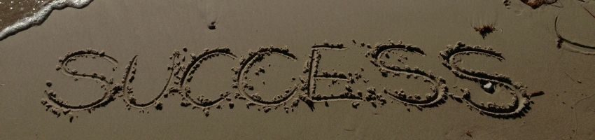 "The word ""success"" written on the sand."